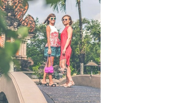 two-women-wearing-sunglasses-and-holding-bags-standing-on